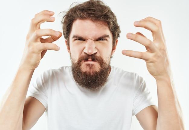 彼の手で身振りで示す感情的なひげを生やした男は、明るい背景を怒らせます。高品質の写真