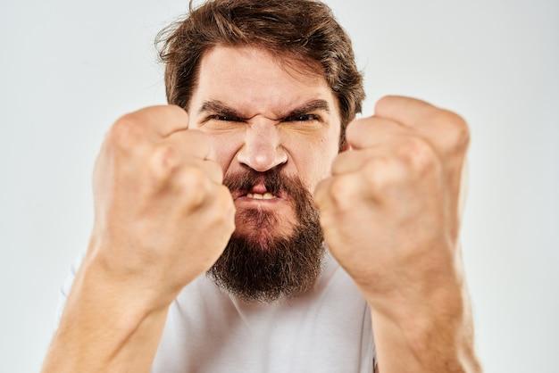 Эмоциональный бородатый мужчина в белой футболке жесты руками на светлом фоне