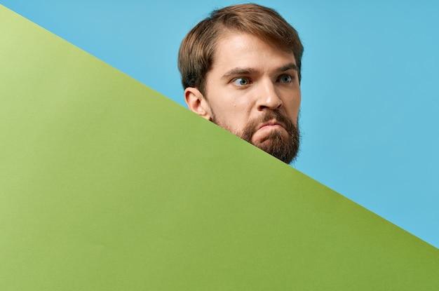 緑のバナースタジオの青い背景の後ろから覗く感情的なひげを生やした男。高品質の写真