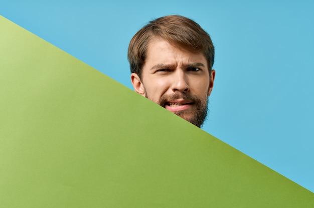 緑のバナースタジオ青い背景の後ろから覗く感情的なひげを生やした男