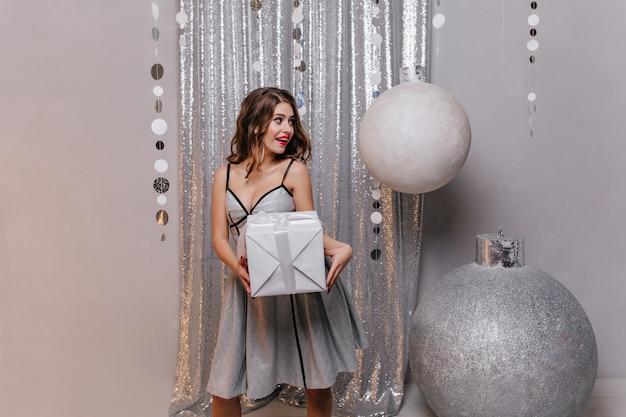 빛나는 드레스에 감성적 인 아름다운 갈색 머리는 그녀의 친구에게 놀라움을 따르고 새해 선물을주고 싶어합니다.