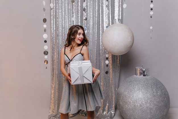 Emotional beautiful brunette in shining dress wants to follow surprise to her friend and give new year's gift.