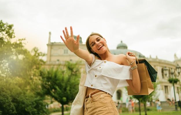 야외에서 카메라에 포즈 종이 쇼핑백과 감정적 인 아름다운 쇼핑 중독 여자