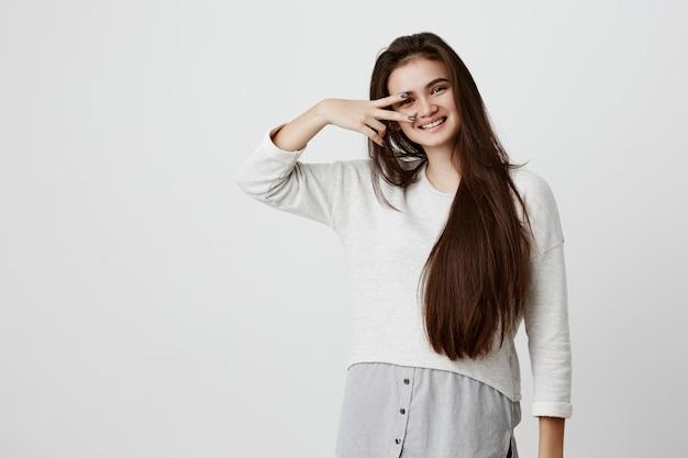 長い黒髪の感情的な美しい女性がさりげなく服を着て、vサインを見せて、灰色の壁にポーズをとって嬉しそうに笑顔します。屋内で楽しんで、肯定的な感情を表現する若いブルネットの女性。
