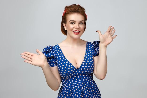 Эмоциональная красивая молодая европейская женщина, одетая как девушка в стиле пин-ап, позирует у глухой стены