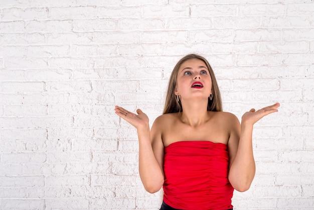 赤いドレスを着た感情的な美しい若い女性