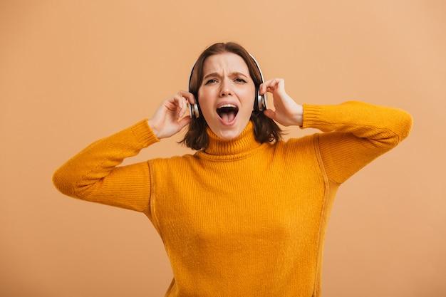 感情的な美しい若い女性が歌っているヘッドフォンで音楽を聴きます。