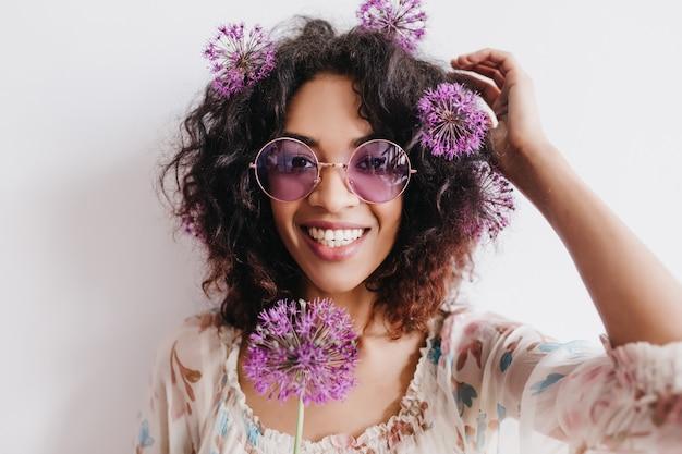 紫色の花でポーズをとって笑っている感情的な黒人女性。ネギを楽しんでいる愛らしいアフリカの女の子の屋内ショット。