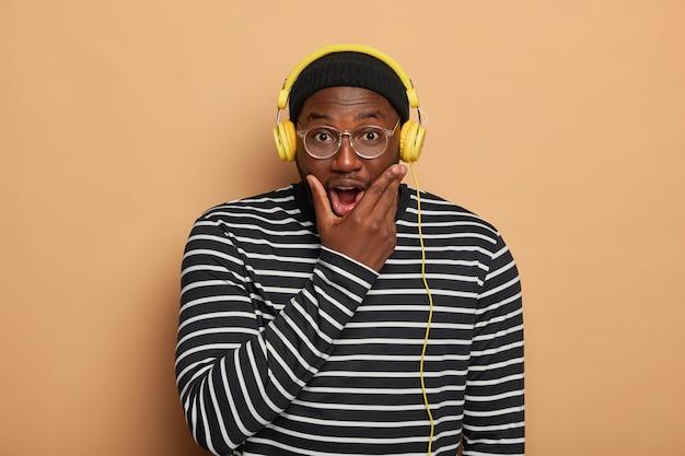 Il giovane nero emotivo tiene il mento, ascolta la traccia audio in cuffie moderne