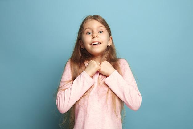 感情的なブロンドの女の子は幸せそうな表情と歯を見せる笑顔を持っています