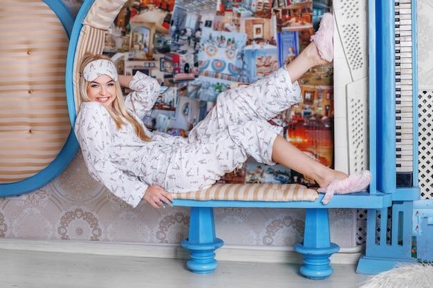 Emotional blonde girl in pajamas. sleep mask.