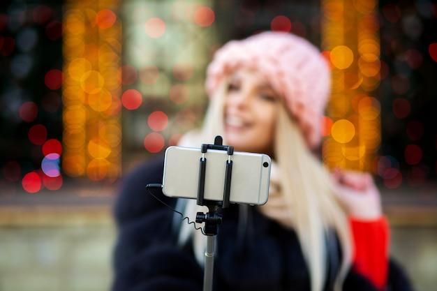 ピンクの帽子をかぶって、花輪で飾られた街の通りで自分撮りをしている感情的なブロンドの女の子。テキスト用のスペース