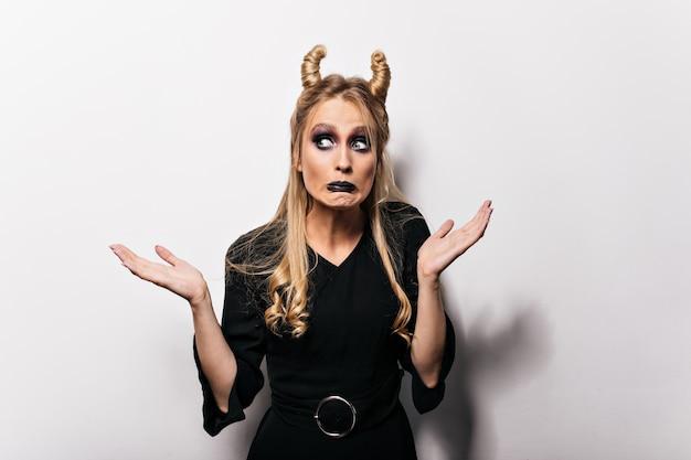 ハロウィーンで面白いポーズをとる感情的なブロンドの女性。白い壁に立っている金髪の魔女。
