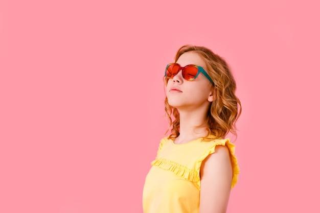 Эмоциональная блондинка в блестящих солнцезащитных очках и желтой футболке смеется в камеру на розовом