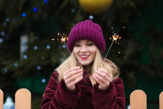 キエフの新年のトウヒで輝くベンガルライトを楽しんでいる感情的なブロンドの女性