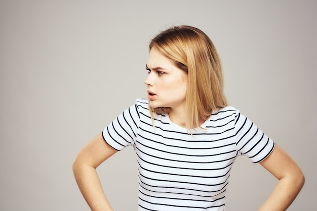 分離されたストライプのtシャツライフスタイルの表情で感情的なブロンドの女性