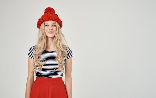 電話のクロップドビューで彼女の頭にキャップが付いたストライプのtシャツの感情的なブロンドの女性。