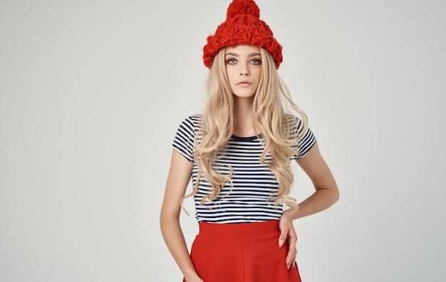 Эмоциональная блондинка в полосатой футболке с кепкой на голове по телефону