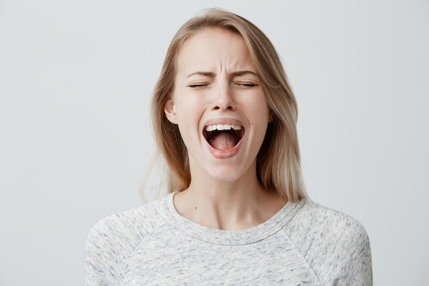 Emotional blonde woman opening her mouth widely screaming loudly being dissatisfied with something expressing disagreement and annoyance