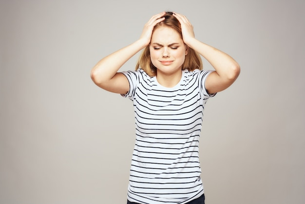 Emotional blonde woman in striped t-shirt lifestyle facial expression.