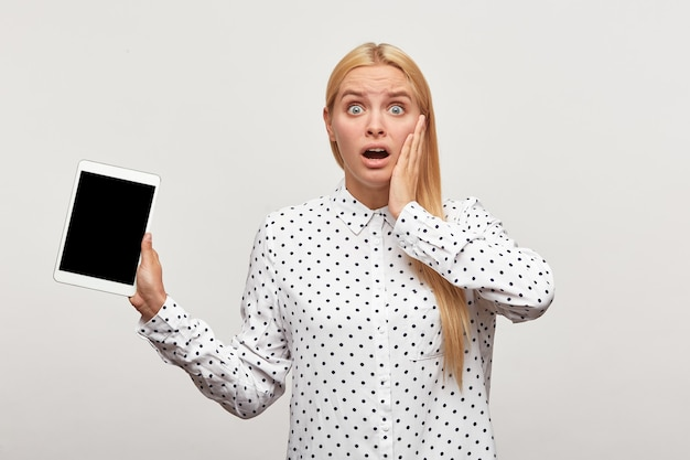 Emotional blonde woman with wide open eyes and mouth, looks shocked with tablet in hand, one hand holding her cheek