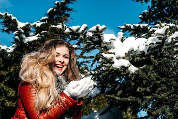 手に雪を吹く感情的な青い目の女の子。凍るような冬。