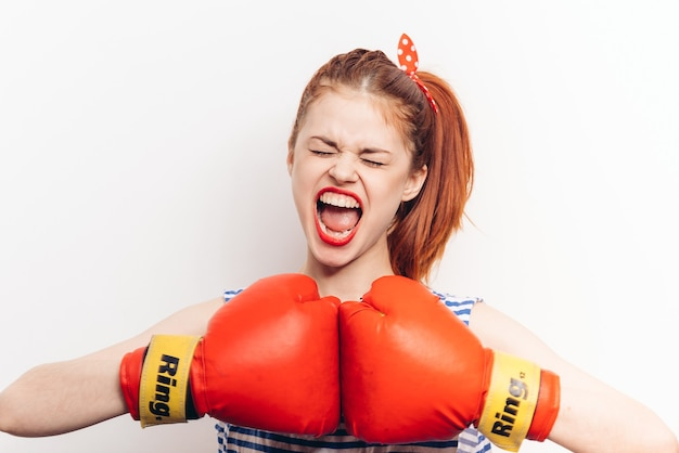 Emotional boxer in gloves and striped t-shirts on a light gesturing with her hands cropped view