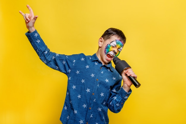 Emotional boy holding karaoke microphone and sing while stay isolated on yellow wall