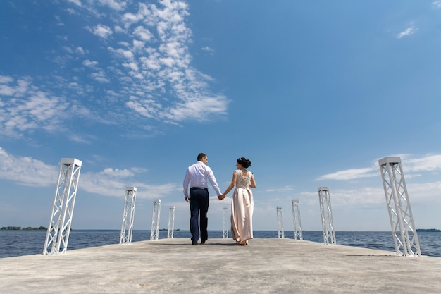 Emotional bride and groom walking on the bridge in sunny day .wedding day. man and woman gentle look each other and holding hands outdoors. romantic moment on the date