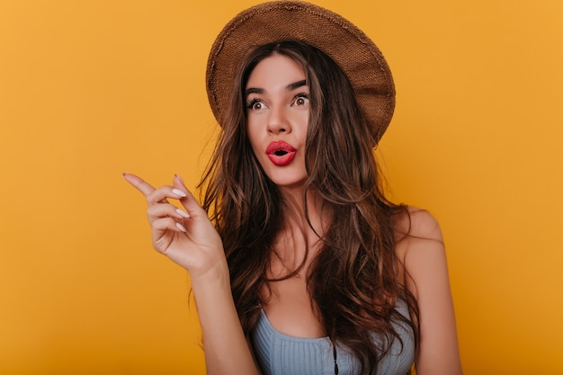 Emotional brown-haired girl with long nails standing on yellow space