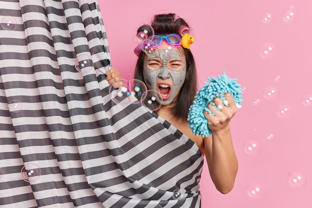 Emotional brunette asian woman shouts loudly applies clay mask holds sponge applies hair rollers hides behind shower curtain poses against pink background with soap bubbles. hygiene concept.