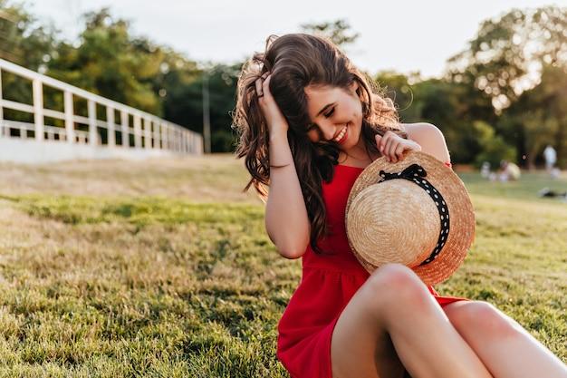 公園で休息を楽しんでいるエレガントな帽子を持つ感情的なブルネットの少女。草の上に座って髪に触れている赤い服装の魅力的な女性。