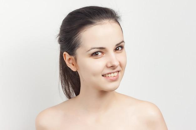 Эмоциональная брюнетка с косметической кистью с открытыми плечами в уходе за кожей рук