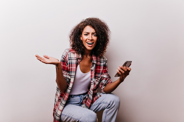 Emotional brunette woman holding smartphone. wonderful african girl posing with device in her hand.