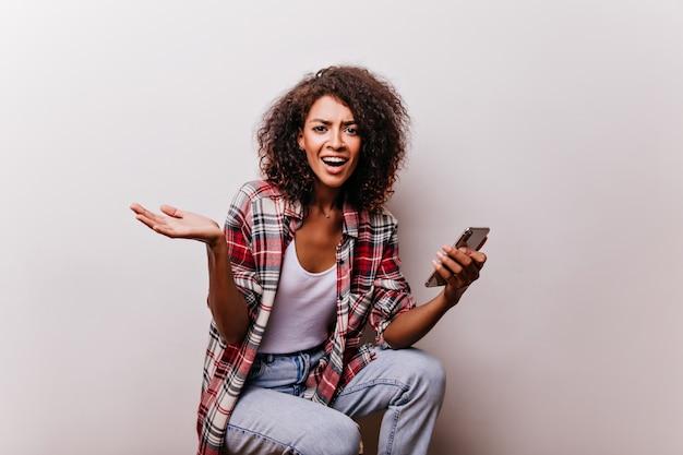 Donna castana emotiva che tiene smartphone. meravigliosa ragazza africana in posa con il dispositivo in mano.