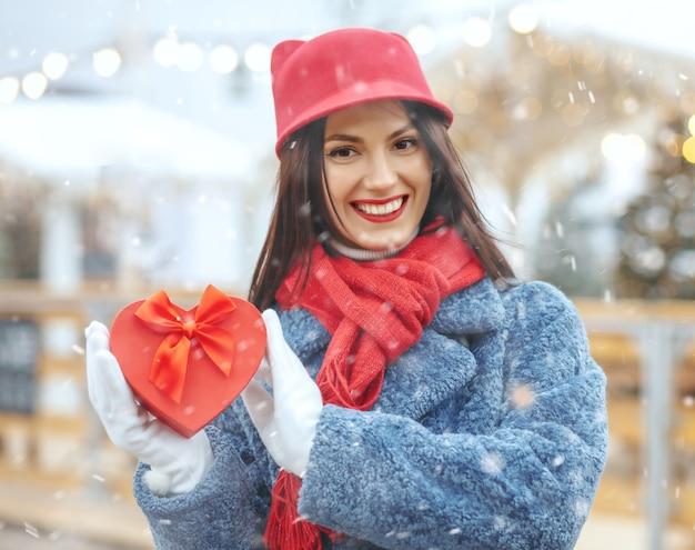 降雪時にクリスマスフェアでギフトボックスを保持している冬のコートの感情的なブルネットの女性