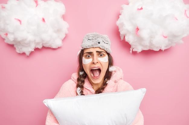 Эмоциональная брюнетка молодая женщина громко кричит, держит рот открытым, носит ночное белье с завязанными глазами