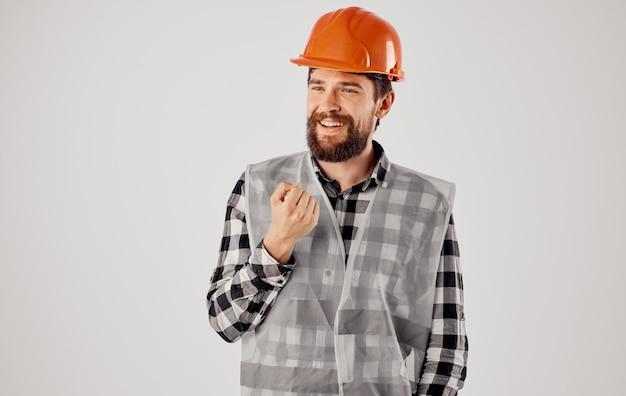 オレンジ色のヘルメットと明るい背景の反射同情の感情的なビルダー。高品質の写真