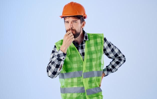 감정적 빌더는 주황색 헬멧 반사 조끼를 손으로 몸짓으로합니다.