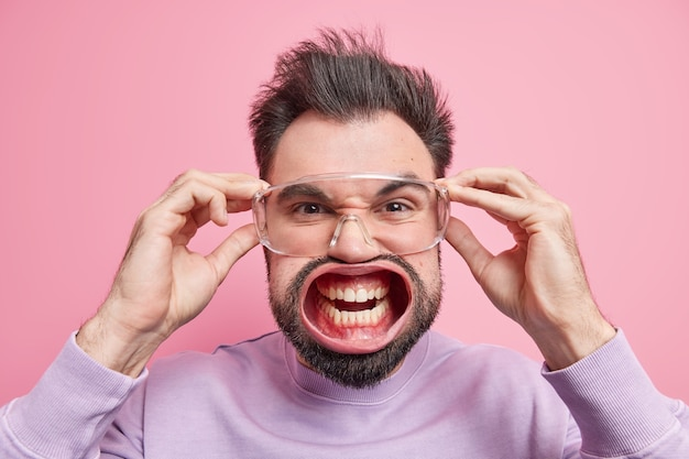 感情的な燃え尽き症候群。あごひげを生やした大人の男のヘッドショットは、巨大な圧力が怒って叫ぶのを感じます歯を食いしばって透明な眼鏡に手を保ちます目を細める顔は怒りを表現します