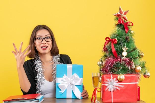 Signora di affari emotiva in vestito con gli occhiali che tiene il suo regalo e seduto a un tavolo con un albero di natale su di esso in ufficio