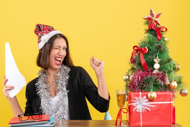 Emotional business lady in suit with santa claus hat and new year decorations holding documents and sitting at a table with a xsmas tree on it in the office