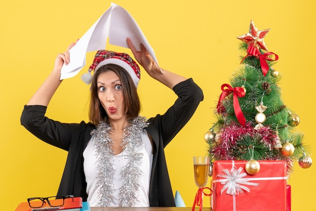Emotional business lady in suit with santa claus hat and new year decorations raising documents on her head and sitting at a table with a xsmas tree on it in the office