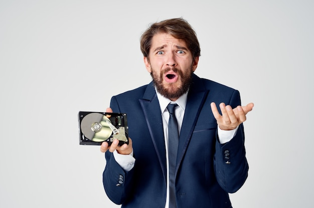 Эмоциональный деловой человек в костюме, жестикулирующий руками и разобранный жесткий диск