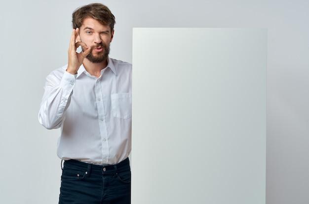 シャツの感情的なビジネスマンは、プロモーション看板を保持します