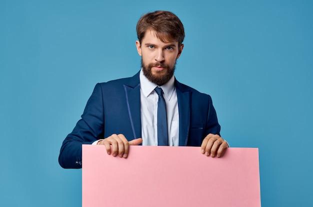 スーツのピンクのバナーモックアッププレゼンテーション青い背景の感情的なビジネスマン。高品質の写真