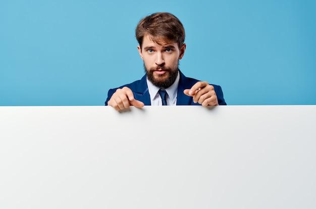 Эмоциональный деловой человек выглядывает из-за баннера обрезанный вид на синем фоне