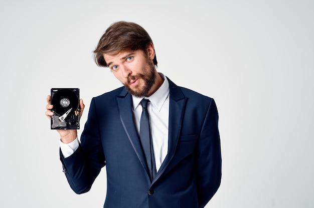 Эмоциональный деловой человек с жестким диском на компьютерных технологиях