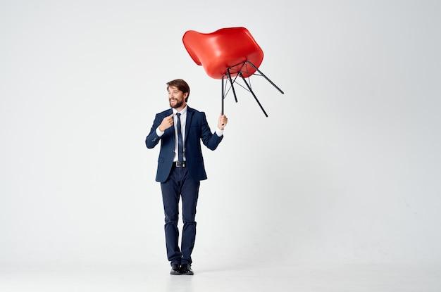オフィスマネージャーの手に赤い椅子を持つ感情的なビジネスマン