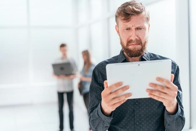 タブレットの画面を見ている感情的なビジネスマン